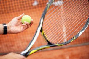 Tennis player prepares to serve ball during tennis match