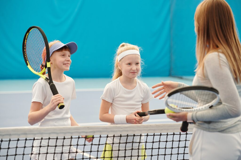 Two happy girls in white sportswear looking at female trainer before playing